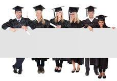 Ομάδα απόφοιτων φοιτητών που παρουσιάζουν το κενό έμβλημα Στοκ Φωτογραφία