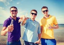 Ομάδα αρσενικών φίλων με τα μπουκάλια της μπύρας στοκ εικόνα