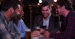 Ομάδα αρσενικών φίλων που χαλαρώνουν μαζί στο φραγμό στεγών απόθεμα βίντεο