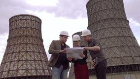 Ομάδα αρχιτεκτόνων που συζητούν ένα σχέδιο κατασκευής για το υπόβαθρο του δροσίζοντας πύργου του πυρηνικού σταθμού άνθρακας φιλμ μικρού μήκους