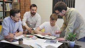 Ομάδα 4 ατόμων στο δημιουργικό γραφείο καταιγισμού ιδεών Νέοι τύποι που μαζεύονται γύρω από τον πίνακα και εμφανισμένοι απόθεμα βίντεο