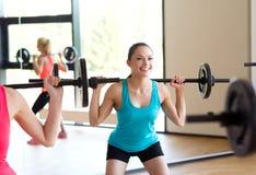 Ομάδα γυναικών με τα barbells στη γυμναστική στοκ εικόνες