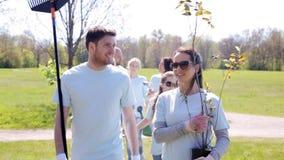 Ομάδα εθελοντών με τα δέντρα και τσουγκράνας στο πάρκο απόθεμα βίντεο