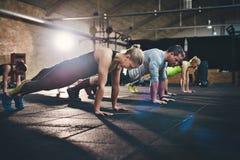 Ομάδα ενηλίκων που κάνουν την ώθηση επάνω στις ασκήσεις Στοκ Εικόνες