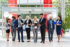 Ομάδα επιχειρηματιών που συζητά το σχέδιο προγράμματος εγγράφων που επικοινωνεί, χαμόγελο που μιλά στο σύγχρονο γραφείο Στοκ εικόνα με δικαίωμα ελεύθερης χρήσης