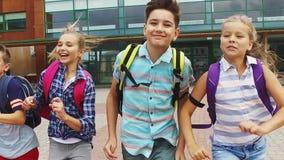 Ομάδα ευτυχούς τρεξίματος σπουδαστών δημοτικών σχολείων απόθεμα βίντεο