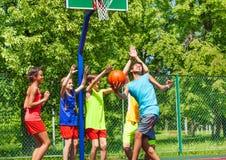 Ομάδα ευτυχών εφήβων που παίζουν την καλαθοσφαίριση Στοκ Εικόνες