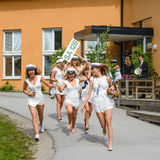Ομάδα ευτυχών εφήβων που φορούν τα καλύμματα βαθμολόγησης που τρέχουν έξω από το σχολείο μετά από τη βαθμολόγηση από το γυμνάσιο  Στοκ Φωτογραφία
