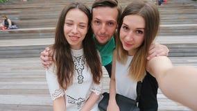 Ομάδα ευτυχών φίλων εφήβων που γελούν και που παίρνουν ένα selfie στην οδό Τρεις φίλοι που προσέχουν παίρνοντας τις εικόνες με απόθεμα βίντεο