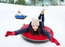 Ομάδα ευτυχών φίλων που γλιστρούν κάτω στους σωλήνες χιονιού Στοκ Εικόνες