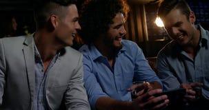Ομάδα ευτυχών φίλων που εξετάζουν το κινητό τηλέφωνο απόθεμα βίντεο