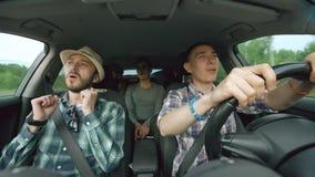 Ομάδα ευτυχών φίλων στο αυτοκίνητο που τραγουδά και που χορεύει ενώ οδικό ταξίδι κίνησης απόθεμα βίντεο