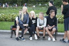 Ομάδα εφήβων που κάθονται στον πάγκο Τα κορίτσια κάθονται στην περιτύλιξη του αγοριού Στοκ Φωτογραφία