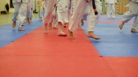 Ομάδα εφήβων karateka στα τρεξίματα κιμονό στο tatami στη γυμναστική απόθεμα βίντεο