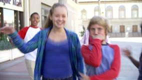 Ομάδα εφηβικών παιδιών που θέτουν για τη κάμερα στη λεωφόρο αγορών απόθεμα βίντεο
