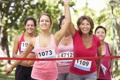Ομάδα θηλυκών αθλητών που ολοκληρώνουν τον αγώνα μαραθωνίου φιλανθρωπίας Στοκ εικόνα με δικαίωμα ελεύθερης χρήσης