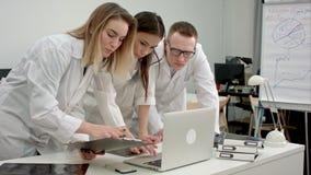 Ομάδα ιατρών που χρησιμοποιεί το lap-top στο γραφείο απόθεμα βίντεο