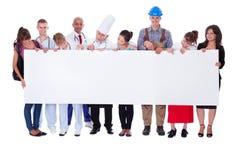 Ομάδα διαφορετικών επαγγελματιών με ένα έμβλημα Στοκ Φωτογραφία