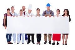 Ομάδα διαφορετικών επαγγελματιών με ένα έμβλημα Στοκ εικόνα με δικαίωμα ελεύθερης χρήσης