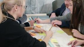 Ομάδα καταιγισμού ιδεών νέας συνεδρίασης των ομάδων μικρών επιχειρήσεων αρχιτεκτόνων δημιουργικής στο γραφείο ξεκινήματος που συζ απόθεμα βίντεο