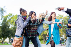 Ομάδα κοριτσιών που απειλείται με το πυροβόλο όπλο από το ληστή Στοκ Εικόνες
