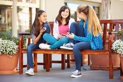 Ομάδα κοριτσιών που κάθονται στη λεωφόρο που χρησιμοποιεί τα κινητά τηλέφωνα Στοκ Εικόνες