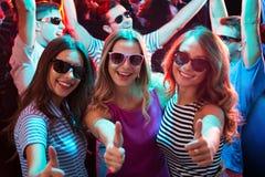 Ομάδα κοριτσιών που χορεύουν κοντά στους φίλους και που παρουσιάζουν ΕΝΤΑΞΕΙ σημάδι Στοκ εικόνα με δικαίωμα ελεύθερης χρήσης