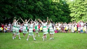 Ομάδα κοριτσιών που χορεύουν σε έναν κύκλο μπροστά από το ακροατήριο στην πράσινη χλόη στο φεστιβάλ απόθεμα βίντεο
