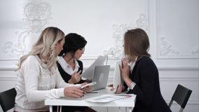 Ομάδα νέων επιχειρησιακών γυναικών που εργάζονται με την ταμπλέτα σε μια συνεδρίαση στο γραφείο απόθεμα βίντεο
