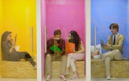 Ομάδα νέων που έχουν τη διασκέδαση, που χαλαρώνουν και που εργάζονται στο δημιουργικό διάστημα Στοκ Εικόνες