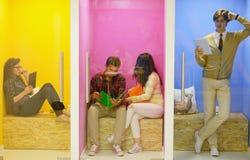 Ομάδα νέων που έχουν τη διασκέδαση, που χαλαρώνουν και που εργάζονται στο δημιουργικό διάστημα Στοκ Εικόνα