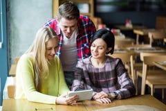 Ομάδα νέων που έχουν τη διασκέδαση στον καφέ Στοκ Εικόνες