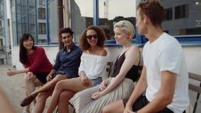 Ομάδα νέων που κάθονται στον καφέ και την ομιλία απόθεμα βίντεο