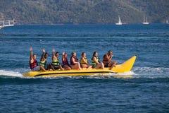 Ομάδα νέων που οδηγούν τη βάρκα μπανανών Στοκ Εικόνες