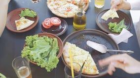 Ομάδα νέων φίλων που απολαμβάνουν ένα γεύμα, που τρώει την πίτσα απόθεμα βίντεο