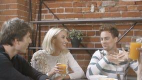Ομάδα νέων φίλων που μιλούν γύρω από έναν πίνακα με τα υγιή πορτοκαλιά ποτά σε μια ημέρα ελεύθερου χρόνου στο σύγχρονο εσωτερικό  απόθεμα βίντεο