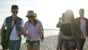 Ομάδα νέων φίλων hipster που περπατούν μαζί σε μια παραλία στην άκρη νερού ` s που κρατά μια κιθάρα Σε αργή κίνηση πυροβολισμός απόθεμα βίντεο