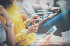 Ομάδα νέων hipsters που κάθονται σε ετοιμότητα EN εκμετάλλευσης καναπέδων και που χρησιμοποιούν την ψηφιακή ταμπλέτα, smartphone  Στοκ Εικόνες