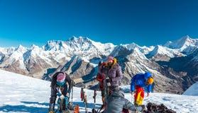 Ομάδα ορειβατών βουνών που προετοιμάζονται για την ανάβαση στην υψηλή αιχμή Στοκ εικόνα με δικαίωμα ελεύθερης χρήσης