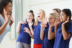Ομάδα παιδιών με το δάσκαλο που απολαμβάνει την κατηγορία δράματος από κοινού Στοκ εικόνες με δικαίωμα ελεύθερης χρήσης