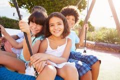 Ομάδα παιδιών που έχουν τη διασκέδαση στην ταλάντευση στην παιδική χαρά Στοκ εικόνες με δικαίωμα ελεύθερης χρήσης