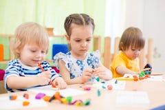 Ομάδα παιδιών που κάνει τις τέχνες και τις τέχνες στο κέντρο ημερήσιας φροντίδας στοκ φωτογραφίες