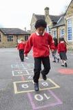 Ομάδα παιδιών που παίζουν Hopscotch στη σχολική παιδική χαρά στοκ φωτογραφίες