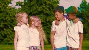 Ομάδα παιδιών που στέκονται στα ζεύγη, που εξετάζουν το ένα το άλλο με προσήλωση και που χαμογελούν στη κάμερα απόθεμα βίντεο
