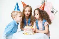 Ομάδα παιδιών στην εορταστική ΚΑΠ που φυσά το κερί, που κάνει μια επιθυμία Εορτασμός το όμορφο κέικ γενεθλίων μπαλονιών αφροαμερι Στοκ εικόνες με δικαίωμα ελεύθερης χρήσης