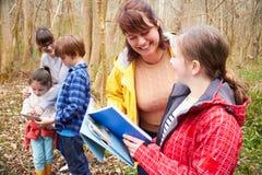 Ομάδα που εξερευνά τα ξύλα στο υπαίθριο κέντρο δραστηριότητας στοκ εικόνες