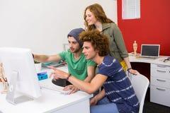 Ομάδα που εξετάζει τη οθόνη υπολογιστή στην αρχή Στοκ εικόνα με δικαίωμα ελεύθερης χρήσης