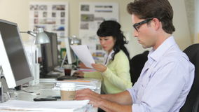 Ομάδα που εργάζεται στα γραφεία στο απασχολημένο γραφείο απόθεμα βίντεο