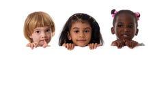 Ομάδα πολυφυλετικού πορτρέτου παιδιών με το λευκό πίνακα απομονωμένος στοκ εικόνα