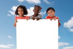 Ομάδα πολυφυλετικού πορτρέτου παιδιών με το λευκό πίνακα στοκ φωτογραφίες